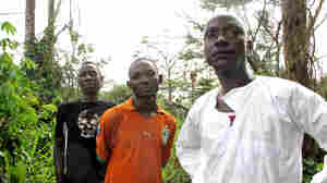 Thieu Patrice, Tan Benjamin and village chief Gueu Denis of Gahapleu, Ivory Coast stand on the secret path into Liberia.