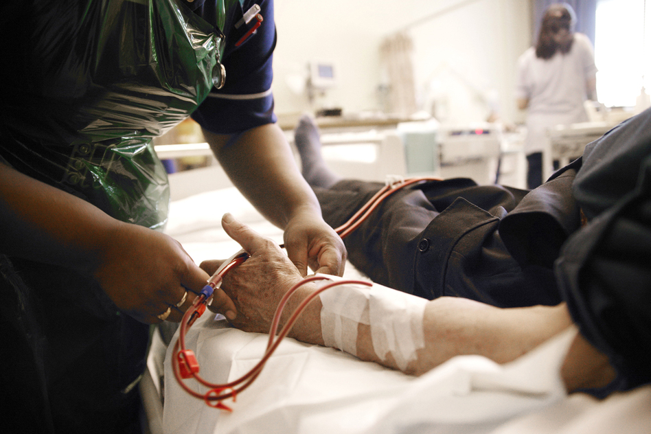 A nurse adjusts the position of a patient's arm during dialysis treatment. The treatment requires trained staff that weren't readily available in the aftermath of Hurricane Sandy. (Michael Donne/Science Source)