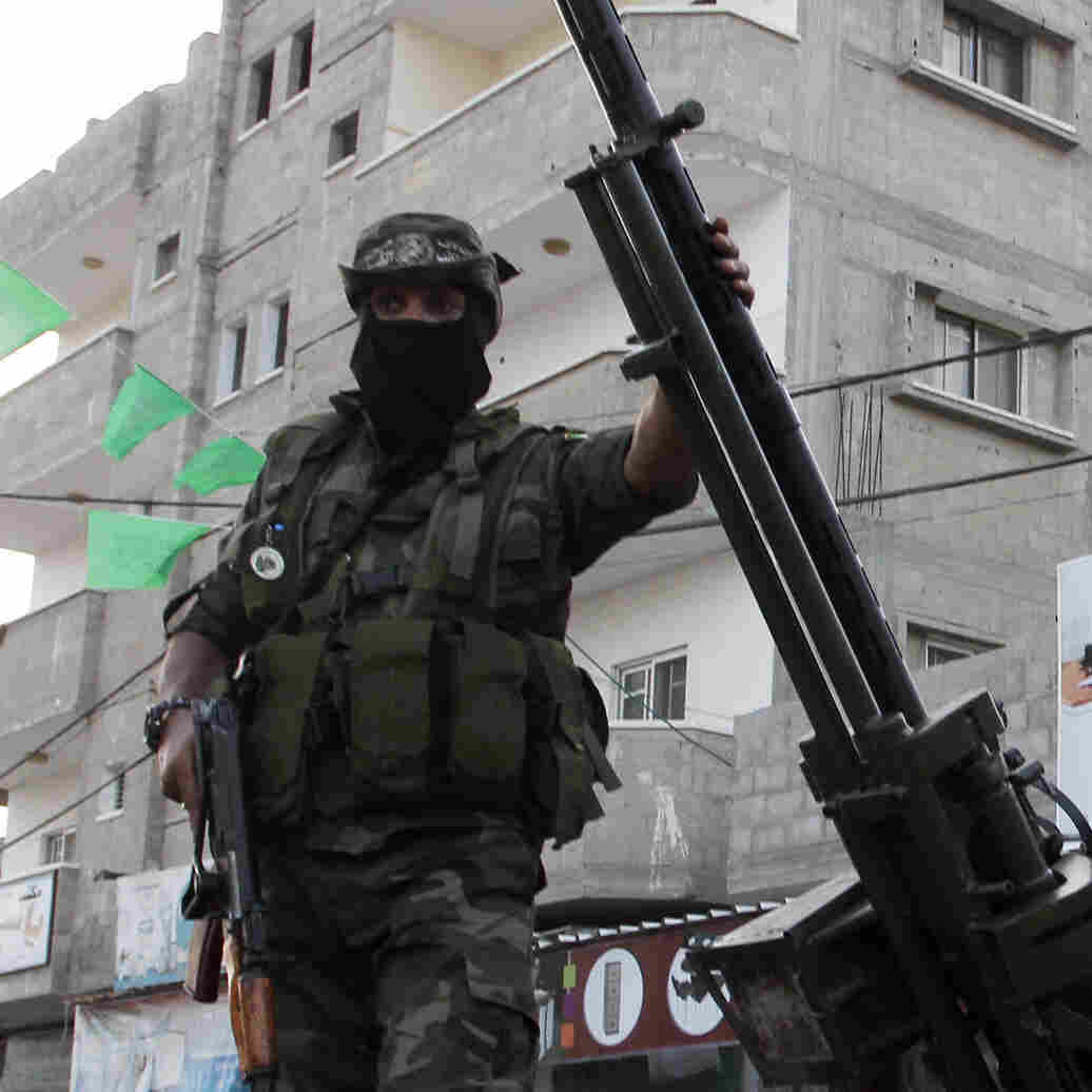 Palestinian members of Hamas' armed wing takes part in a rally Thursday in Rafah, in the southern Gaza Strip. The event was held in memory of Hamas military commanders killed during seven weeks of fighting with Israel in the Gaza Strip this summer.
