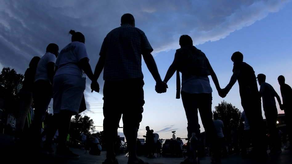 People stand in prayer after a peaceful march on Aug. 20 in Ferguson, Mo., to protest the shooting death of 18-year-old Michael Brown.