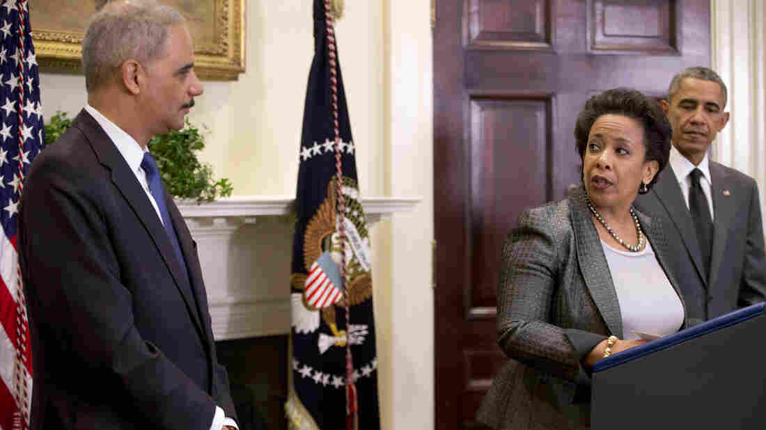 U.S. Attorney General nominee Loretta Lynch, center, looks to outgoing Attorney General Eric Holder as President Obama stands nearby Nov. 8 in the Roosevelt Room of the White House.