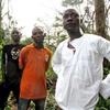 Thieu Patrice, Tan Benjamin and village chief Gueu Denis of Gahapleu, Ivory Coast, stand on the path to Liberia.