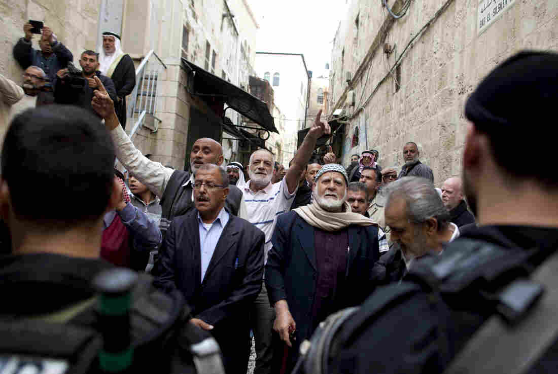 Palestinian men shout slogans next to Israeli police as they await permission to enter what Jews call the Temple Mount and Muslims call the Nobel Sanctuary, on Nov. 5, in Jerusalem, Israel. On Friday, Israel dropped age restrictions on men attending Friday prayers, a move aimed at lowering tensions around access to the contested shrine.