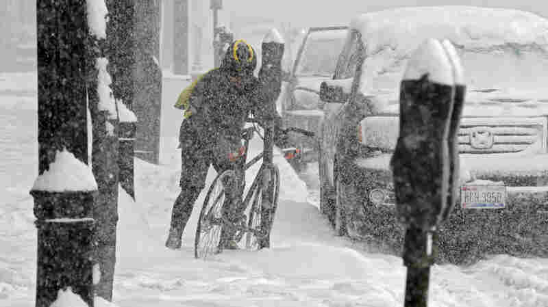 A bicycle messenger struggles through the snow in downtown Cleveland on Friday.