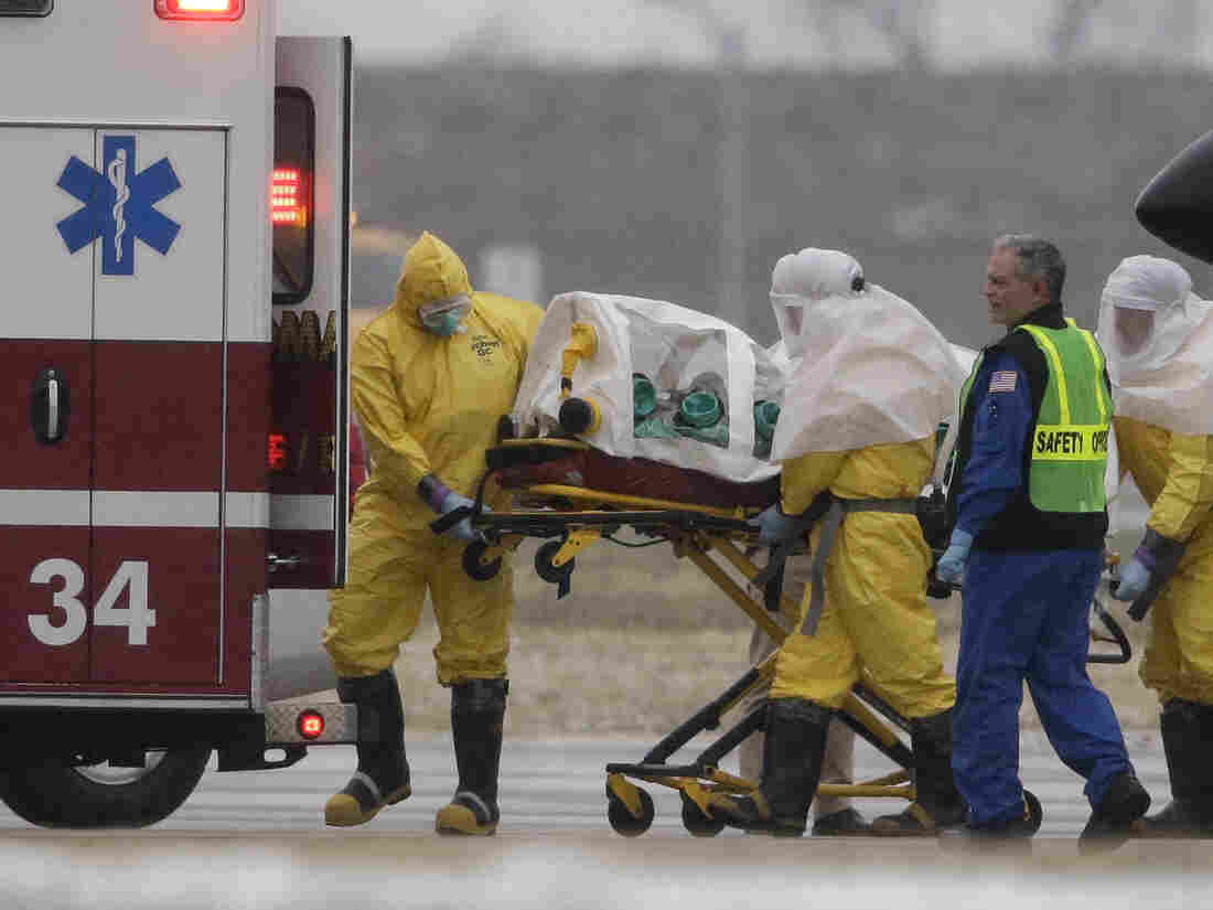 Health workers in protective suits transport Dr. Martin Salia, a surgeon working in Sierra Leone who has been diagnosed with Ebola, from a jet that brought him from Sierra Leone to a waiting ambulance in Omaha, Neb., on Saturday.