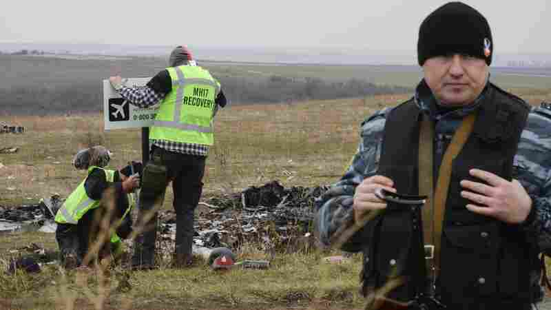 """A pro-Russian rebel fighter guards an area of the Malaysia Airlines Flight 17 crash site in the village of Hrabove, Donetsk region, eastern Ukraine, earlier this week. Investigators erect a """"no trespassing"""" sign in the background."""