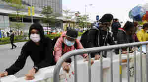 Masked pro-democracy protesters move a barricade farther away from an office tower Tuesday in accordance to a court injunction to clear up part of the protest site, after the arrival of bailiffs outside the government headquarters in Hong Kong. Authorities were preparing to clear part of a key area of the heart of the city that has been occupied by the demonstrators for nearly two months.