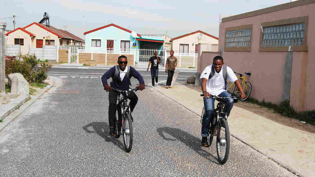 Sizwe Nzima, right, and one of his six employees deliver medicines to patients in a Cape Town neighborhood.