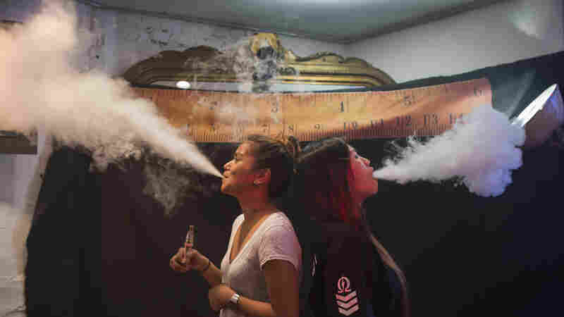 """Vape was chosen as the word of the year for 2014 in part because it provides a window """"onto how we define ourselves,"""" says Casper Grathwohl of the Oxford University Press. Here, women exhale vapor clouds during a competition at the Henley Vaporium in Manhattan."""