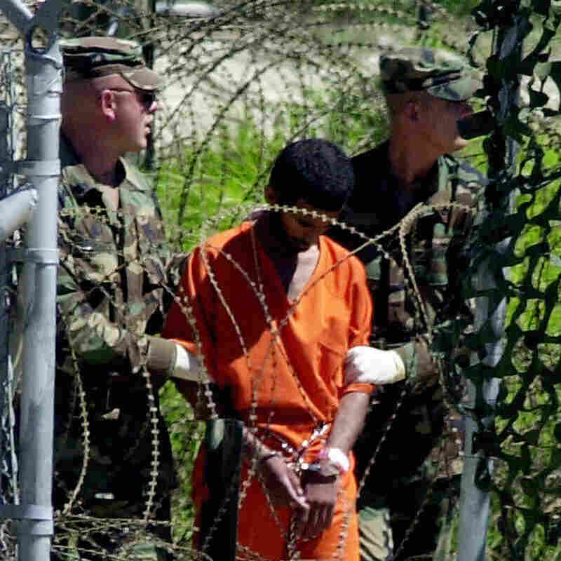 A detainee is escorted in March 2002 by two Army military police at Guantanamo Bay, Cuba. The detainee was being led to the Joint Interrogation Facility to be interviewed by government investigators.
