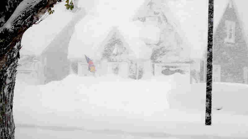 A house is obscured by windblown, lake-effect snow on Tuesday.