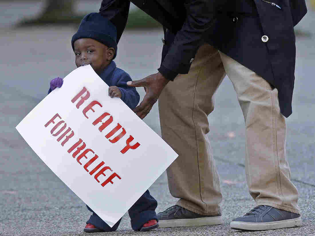 One-year-old Lavon Massey holds a sign as part of a protest outside the U.S. Citizenship and Immigration Services office in New Orleans on Wednesday. Organizers were drawing attention to the possibility that many undocumented immigrants may not be shielded by the president's executive order.