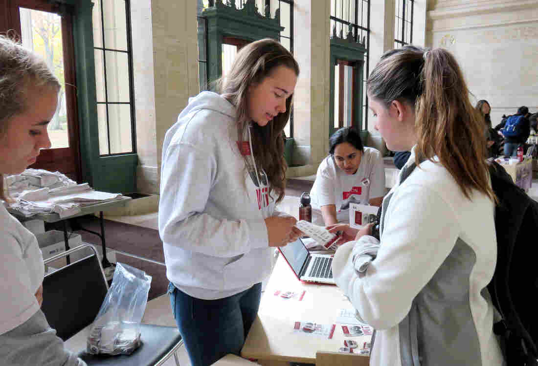 "MIT student activist Larkin Sayre (center) works a booth representing the ""It's on Us"" campaign in a lobby on campus."