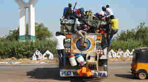 Civilians who had just recently arrived in Yola prepare to flee again, this time in a large open-top truck headed to the