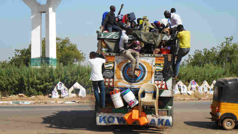Civilians who had just recently arrived in Yola prepare to flee again, this time in a large open-top truck headed to the city of Jos.
