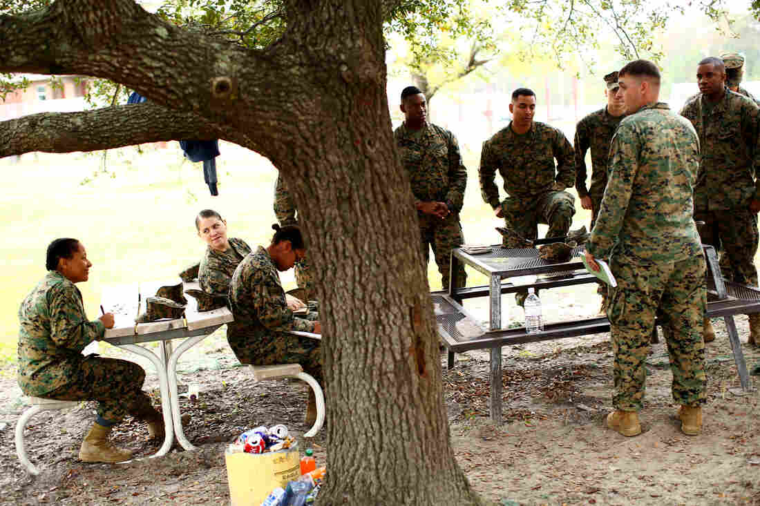 Male and female Marines gather for class in a courtyard outside the barracks.