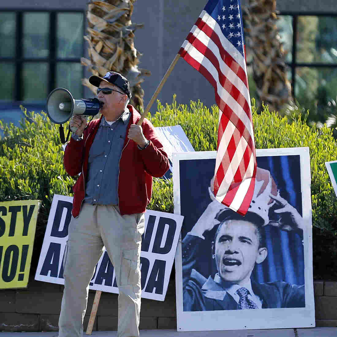 An anti-Obama protester yells on a megaphone Friday across the street from Del Sol High School in Las Vegas, where President Obama delivered remarks on his use of executive authority to relax U.S. immigration policy in Las Vegas.
