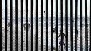 People walk along the beach in Tijuana, Mexico, near San Diego, where metal bars marking the border with the U.S. meet the sea.