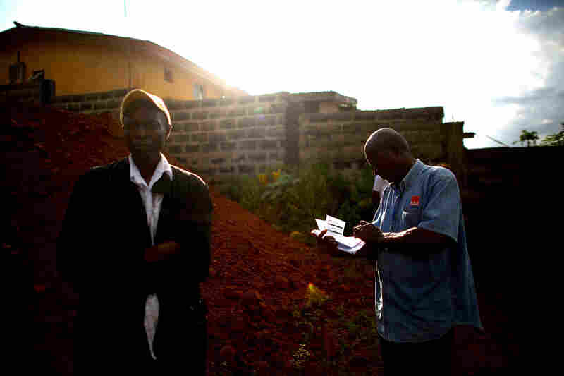 Surveillance team leader Tommy Bangura, right, writes up information about a suspected Ebola case. This week alone, 234 new cases were confirmed in Freetown.