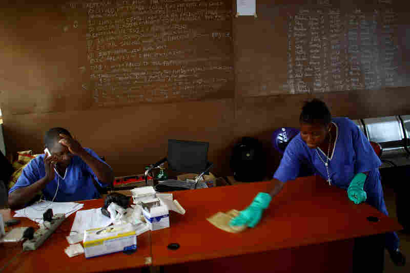 Dr. Komba Songu M'Briwah, left, talks on the phone while staff members disinfect the offices at the Hastings Ebola Treatment Center.