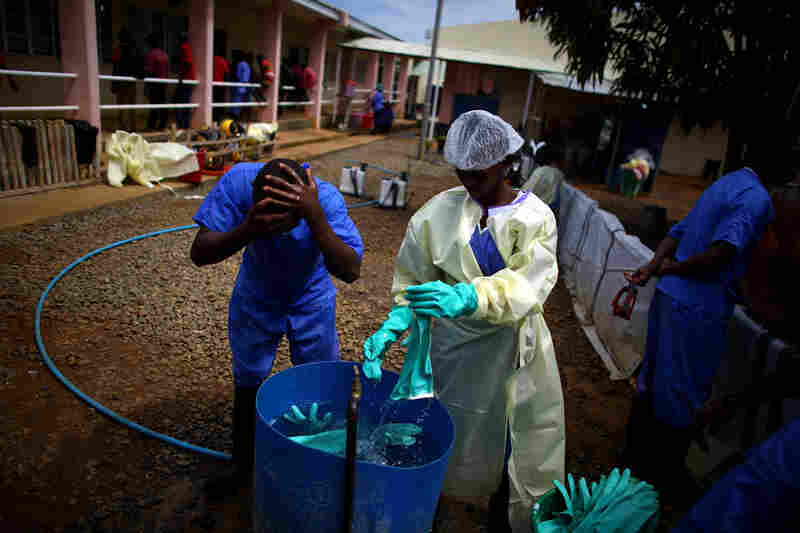 Support staff wash both themselves and and their equipment after leaving the high-risk areas of the treatment center.