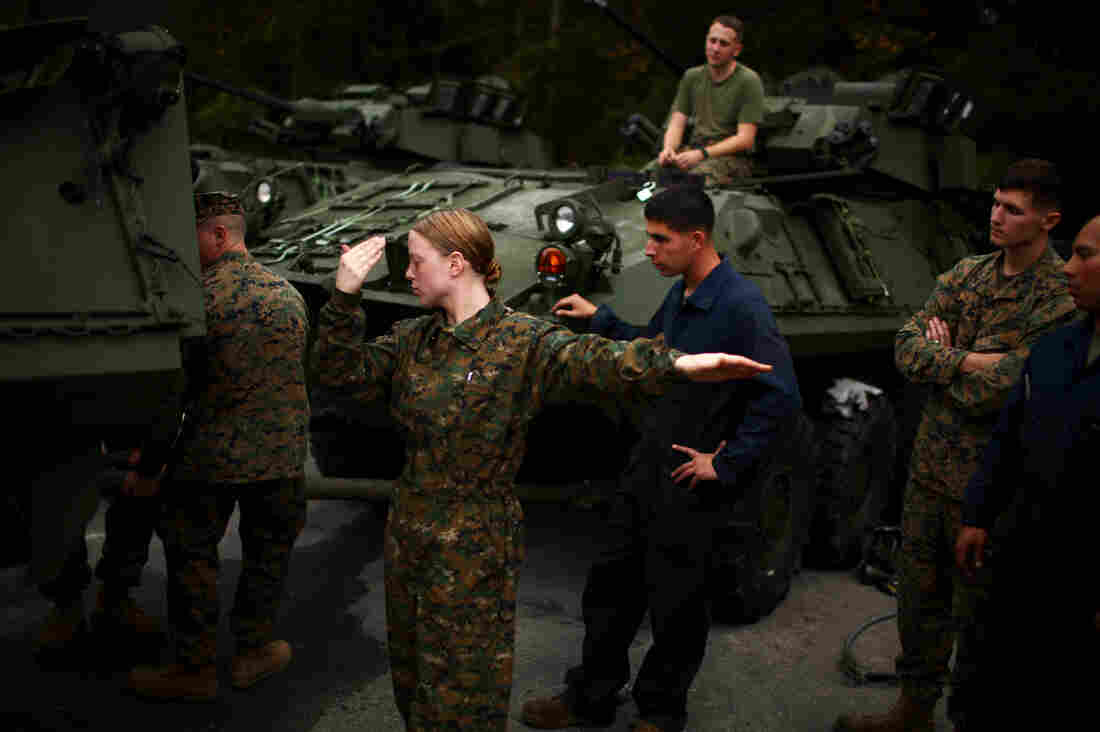 Lance Cpl. Brittany Holloway helps to direct the driver of a light armored vehicle during training at Camp Lejeune, where female Marines are enduring the same training as their male counterparts for combat arms.