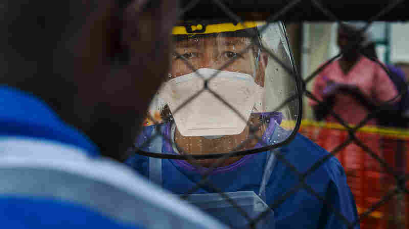 """Wencke Petersen, a Doctors Without Borders health worker, talks to a man through a chain link gate in September, when she was doing patient assessment at the front gate of an Ebola treatment unit. """"There were days we couldn't take any patients at all,"""" she tells NPR."""