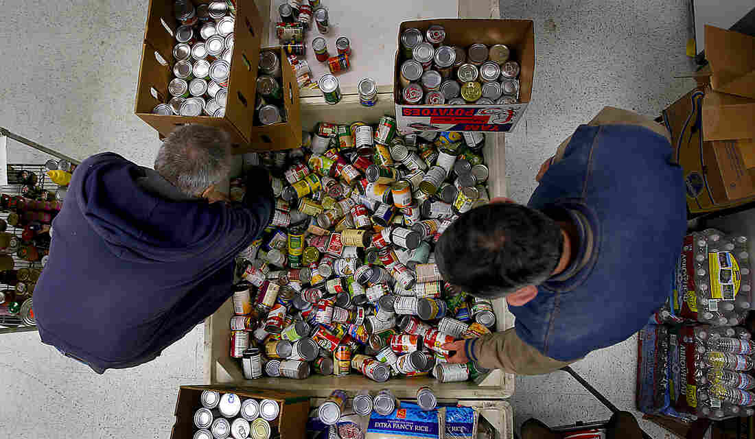 John Umland (left) and John Torrens gather donated cans of food in 2011 in Rohnert Park, Calif., for the group Neighbors Organized Against Hunger. Hunger advocates say a lot of nutritionally dense food like canned tuna and beans can be cheaper than processed food.