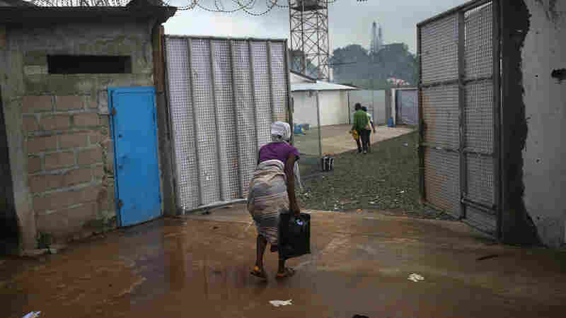 A woman enters the Ebola treatment center at the Island Hospital outside of Monrovia, Liberia, Oct. 6. She said she was bleeding heavily from a miscarriage and was turned away from other clinics in the city.