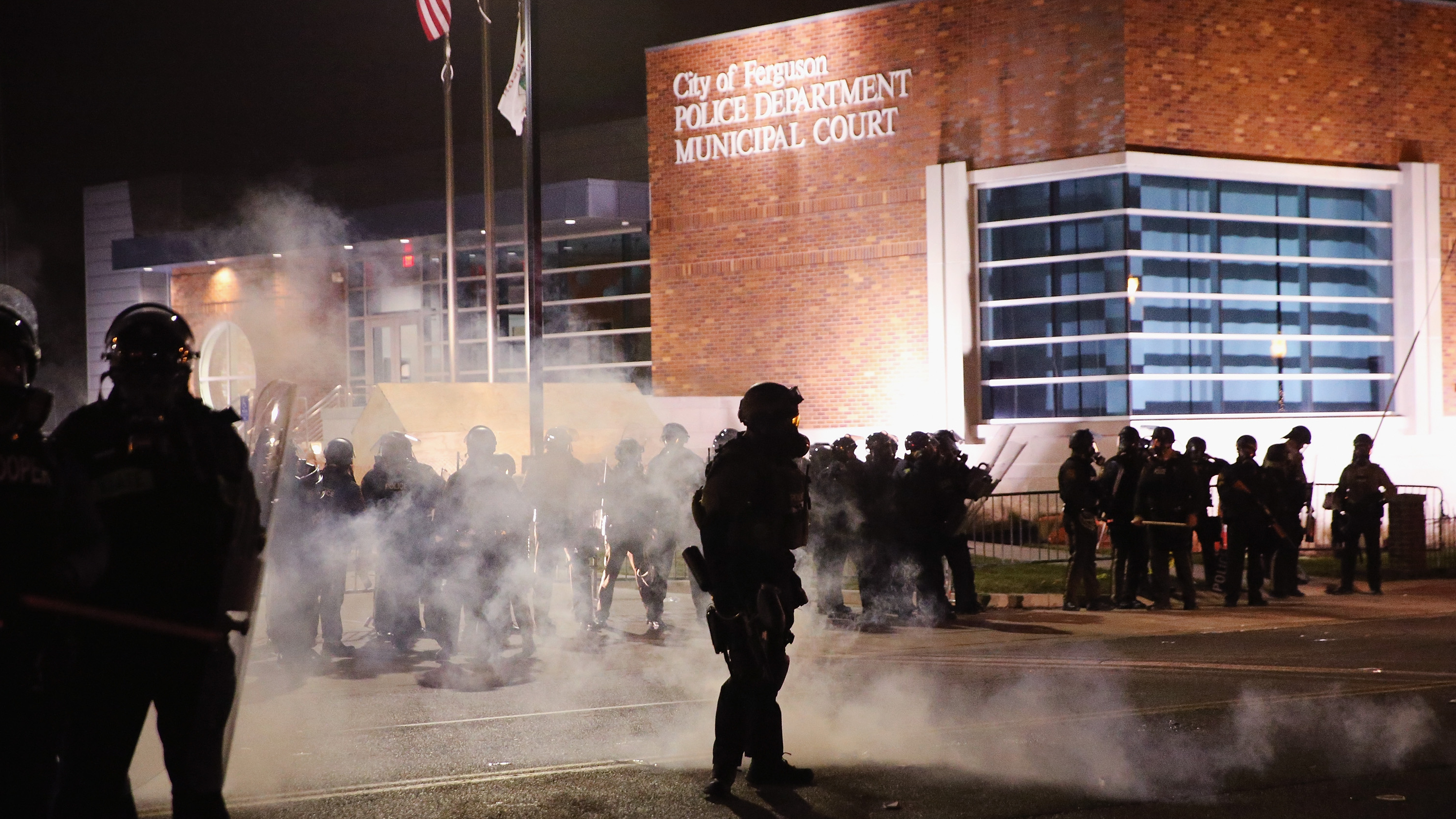 Police guard the Ferguson police department as rioting erupts following the grand jury announcement in the Michael Brown case on Monday in Ferguson, Mo.