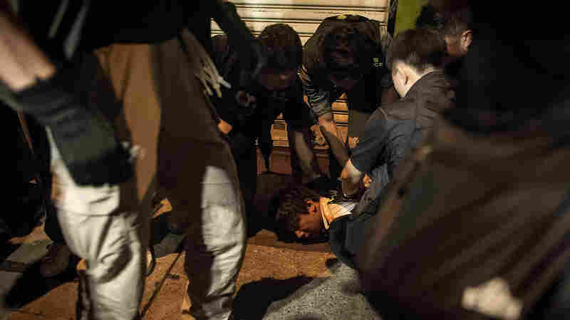 Police officers arrest a protester early Wednesday on a street in the Mongkok district of Hong Kong.