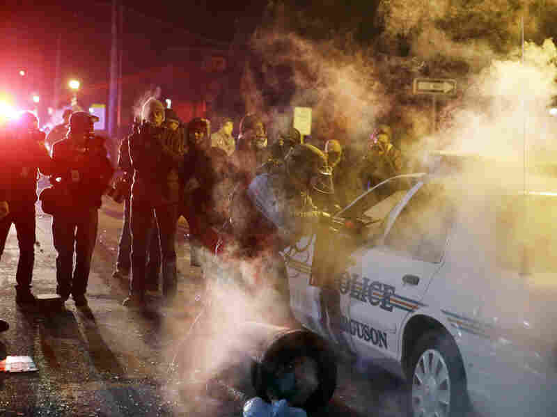 A police officer approach a police vehicle Tuesday night in Ferguson, Mo., after a protester threw an incendiary device onto it.