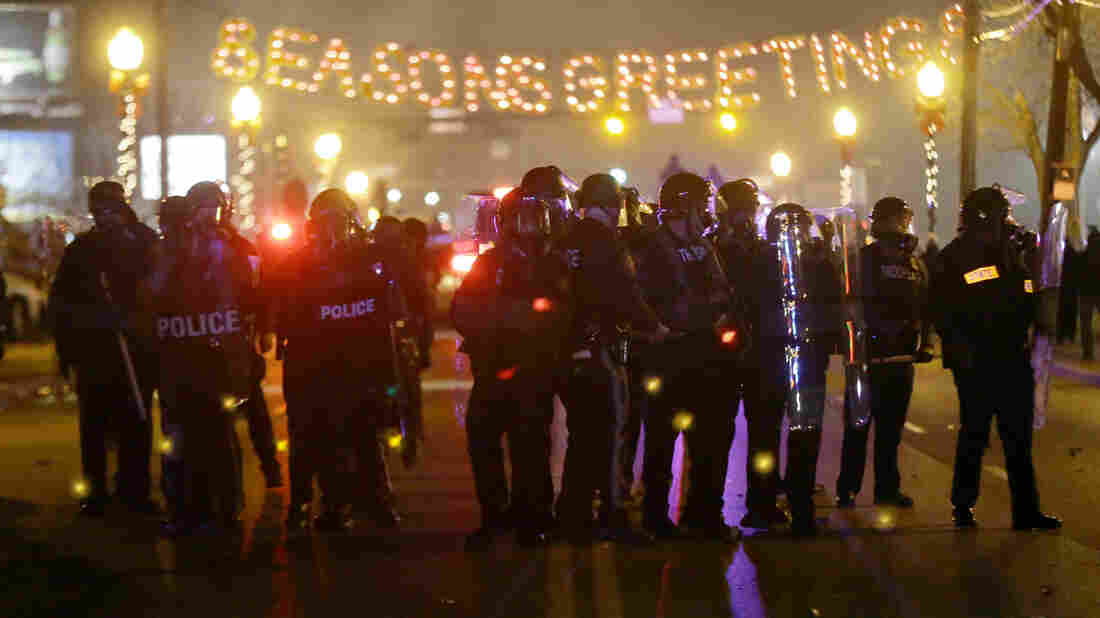 Police gather on the street as protesters react after the announcement of the grand jury decision Monday in Ferguson, Mo. A grand jury decided not to indict Ferguson police Officer Darren Wilson in the death of Michael Brown, the unarmed, black 18-year-old whose fatal shooting sparked sometimes violent protests.