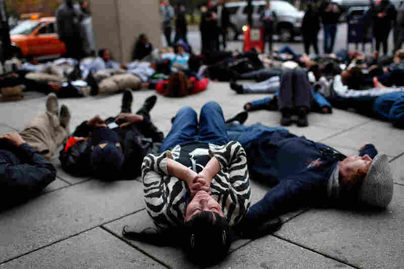 "Joy Cooney takes part in a ""die-in"" during a protest outside the Office of Police Complaints as part of a planned ""28 Hours for Mike Brown"" in Washington, D.C."