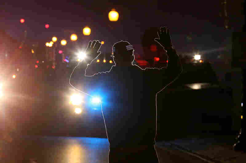 A protester stands in front of police vehicles with his hands up during a demonstration in Ferguson. More than 80 people were arrested in the St. Louis area.