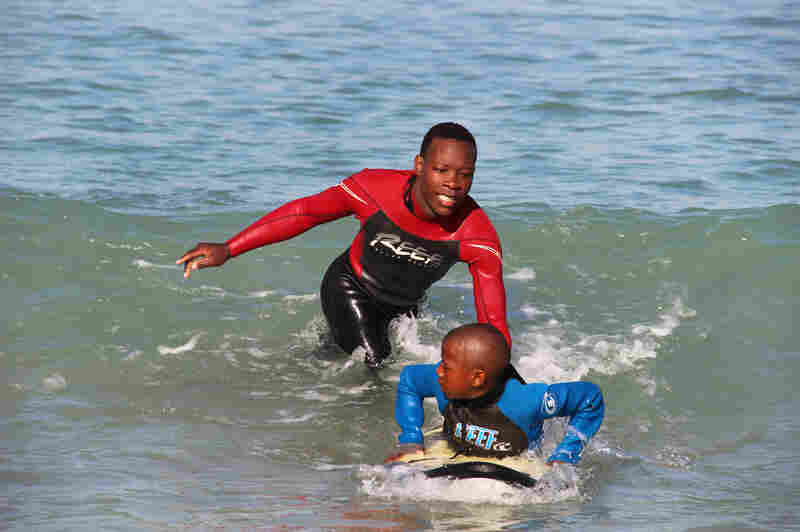 "Lwandile Mntanywa helps a younger surfer learn to catch a wave. He's a ""junior leader"" in the Waves for Change program."