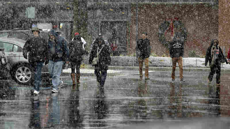 People walk through falling snow Wednesday at a rest stop on Interstate 95 outside Baltimore, in Aberdeen, Md.