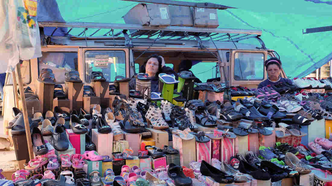 A woman waits for customers at a street market where she sells shoes in Sao Paulo. Brazil and other Latin American economies have prospered by selling commodities and low-tech goods. But now many economies are struggling, and some point to the region's lack of high-tech and other cutting-edge industries.