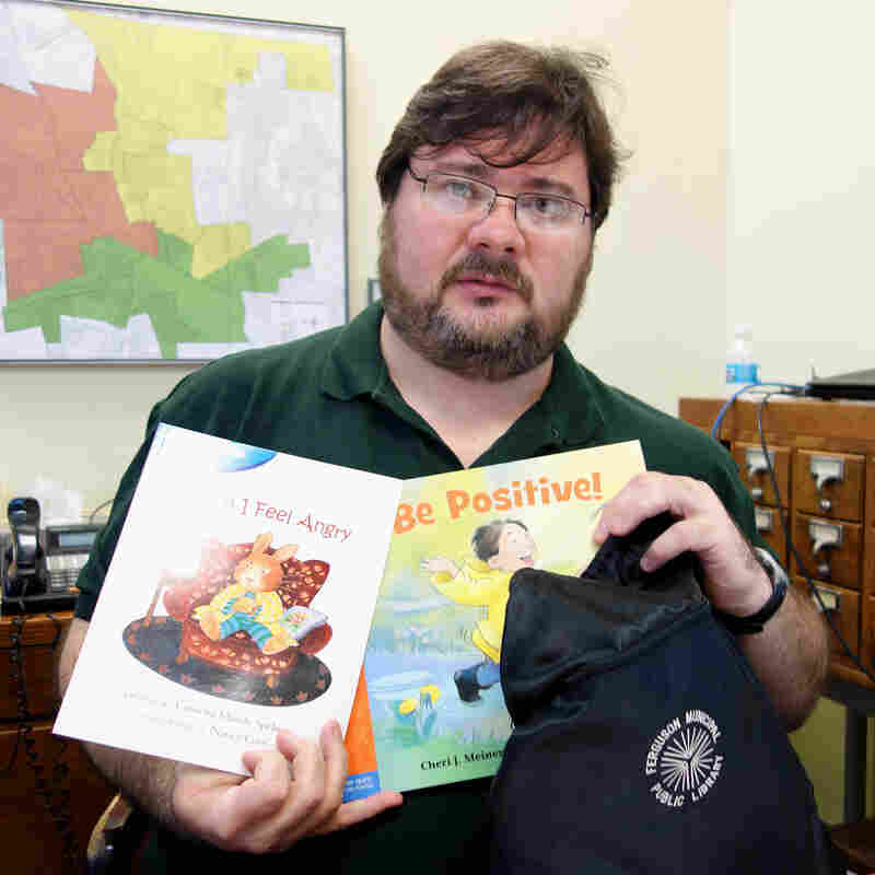 """Scott Bonner, the Ferguson Public Library's director and its only full-time librarian, holds one of the """"healing kits"""" that kids can check out."""
