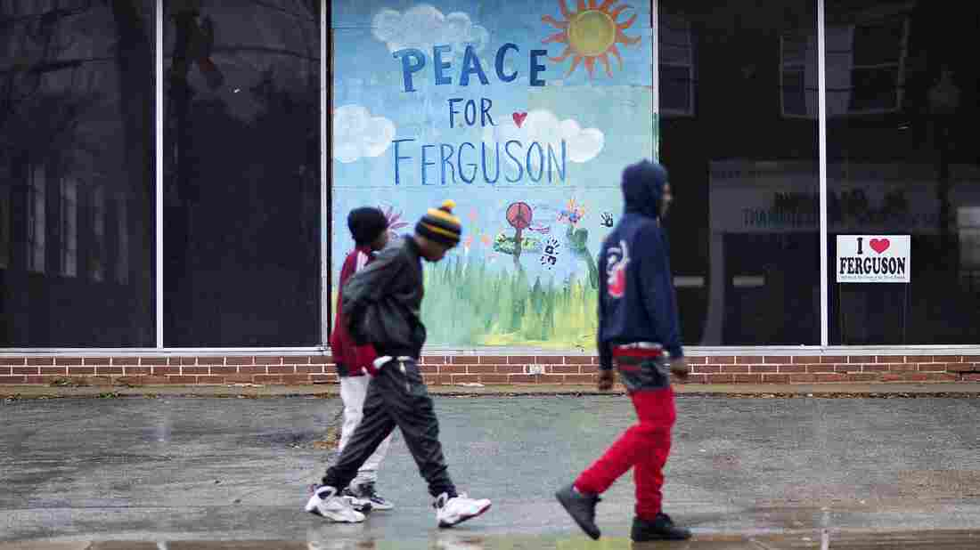 Youths walk past a mural calling for peace in Ferguson, Mo., on a building up the street from the city's police department a day before the grand jury decision was announced.