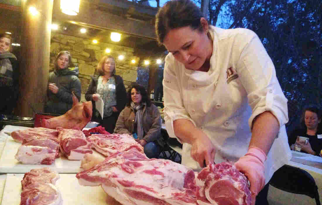 """Master butcher Kari Underly cuts into a hog during a """"Women in the Meat Business"""" workshop in Chapel Hill, NC."""