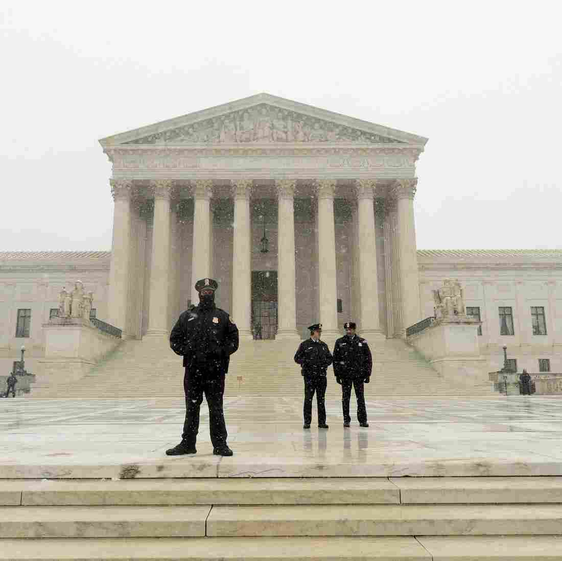 Supreme Court police stand guard during a storm in March.