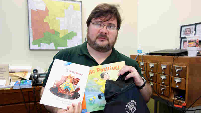 "Scott Bonner, the Ferguson Public Library's director and its only full-time librarian, holds one of the ""healing kits"" that kids can check out."