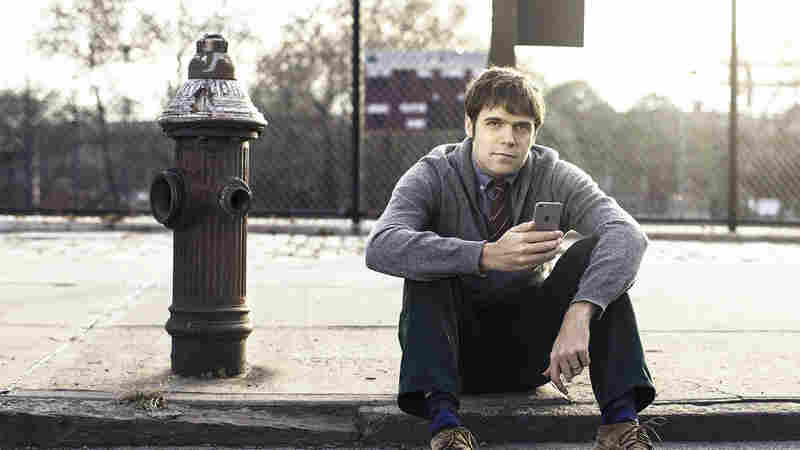New York data blogger Ben Wellington sits next to a fire hydrant Sunday in Brooklyn, N.Y. His investigation into the city's parking ticket data found that two Lower Manhattan hydrants on consecutive blocks in Manhattan generated $55,000 a year for the city — off of cars that appeared to be parked legally.