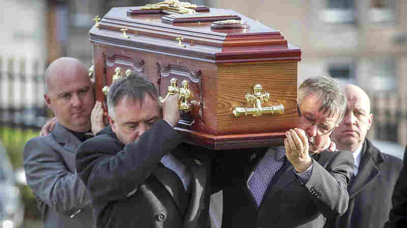 The remains of Brendan Megraw are carried to St. Oliver Plunkett Church in Belfast by his brothers on Nov. 14. The remains were found in a bog 36 years after Megraw was taken by the IRA during the Troubles.