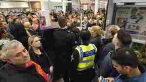 Police are on guard as shoppers line up for a Black Friday sale at a Tesco store in Cardiff, Britain.