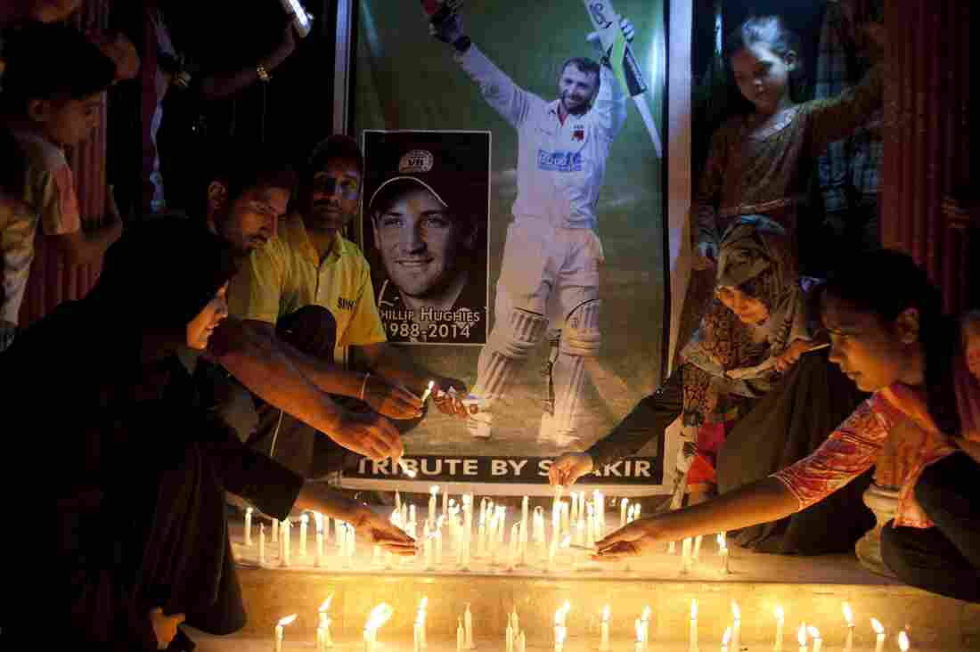 Pakistani cricket fans light candles to pay tribute to Australian cricketer Phillip Hughes in Karachi, Pakistan, on Thursday. Hughes, 25, died in a Sydney hospital Thursday, two days after being struck on the neck by a cricket ball.