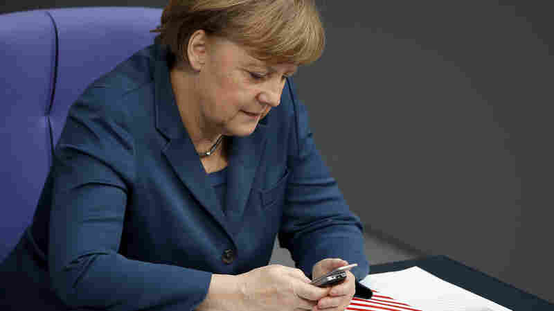 German Chancellor Angela Merkel uses a mobile phone during a meeting of the German federal parliament in Berlin, on Nov. 28, 2013. The country's labor minister supports a call that would prohibit employers from sending emails to employees after normal business hours.