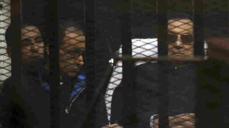 Ousted Egyptian President Hosni Mubarak, 86, lies on a gurney next to his son, Gamal, second left, in the defendants cage, during a court hearing in Cairo, on Saturday. He and his sons saw earlier convictions on murder overturned by the court.