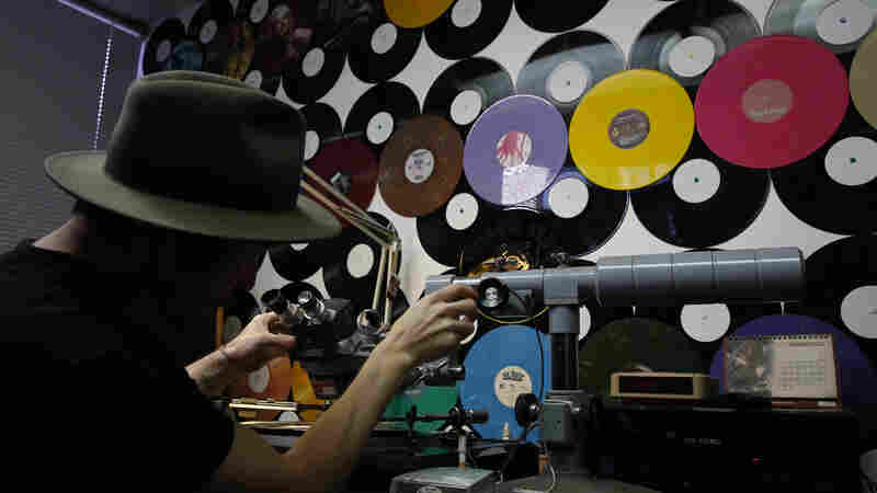 An employee demonstrates how a mother is checked for sound quality before it is duplicated during production at the Rainbo Records factory in Canoga Park, Calif. The vinyl record industry has seen an uptick in sales in recent years, keeping manufacturers like Rainbo busy.